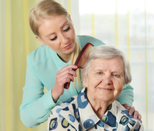 nurse grooming an elderly woman's hair