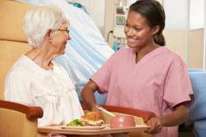nurse serving food to an elderly woman