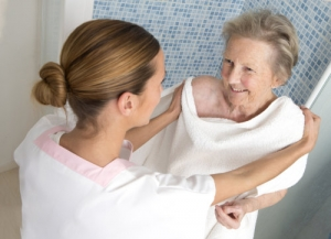 caregiver assisting an elderly woman in the bathroom