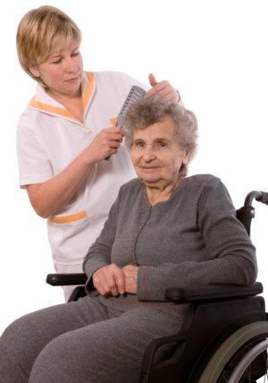 nurse grooming an elderly woman's hair