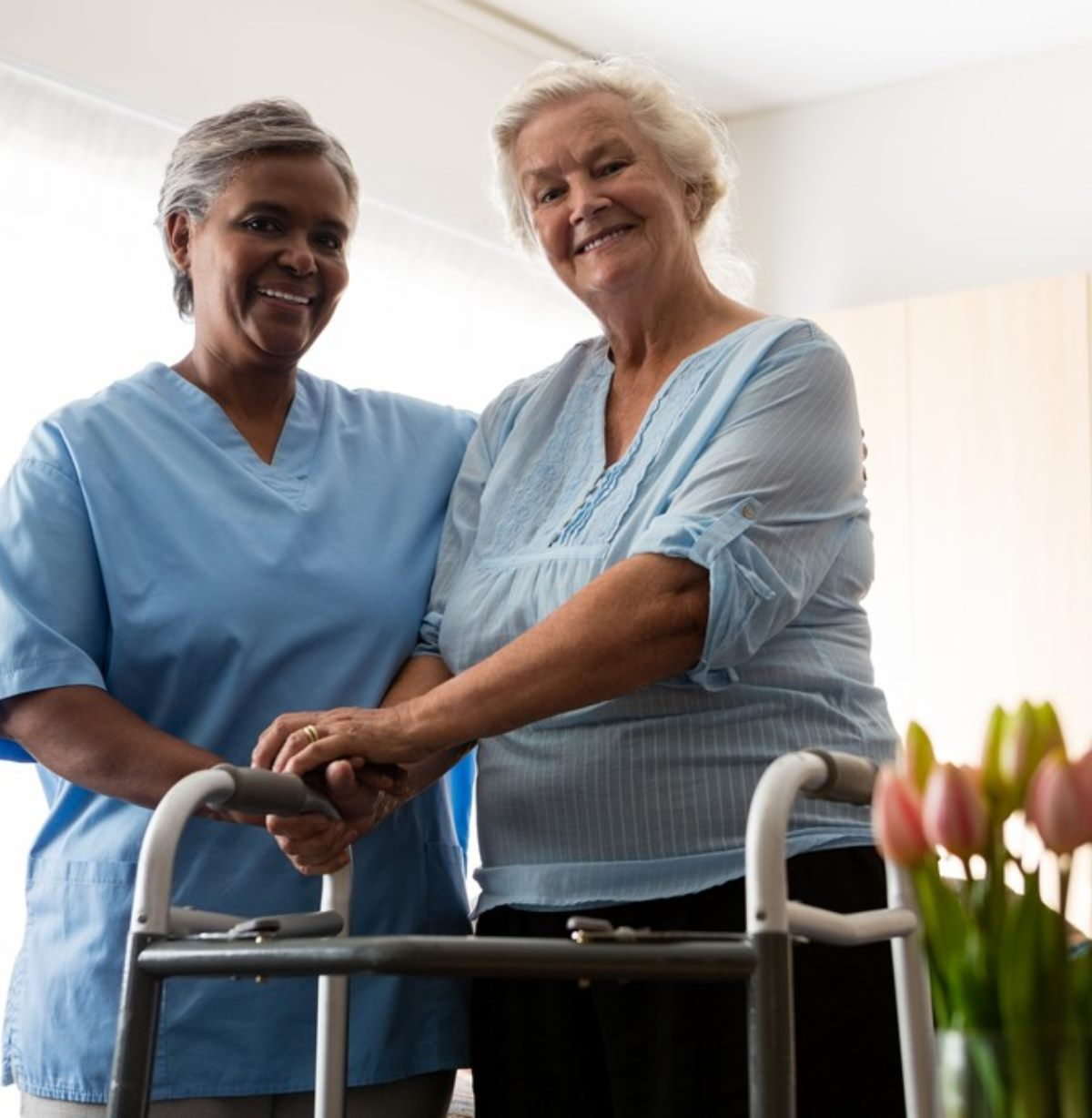 Portrait of nurse standing by senior woman holding walker in nursing home