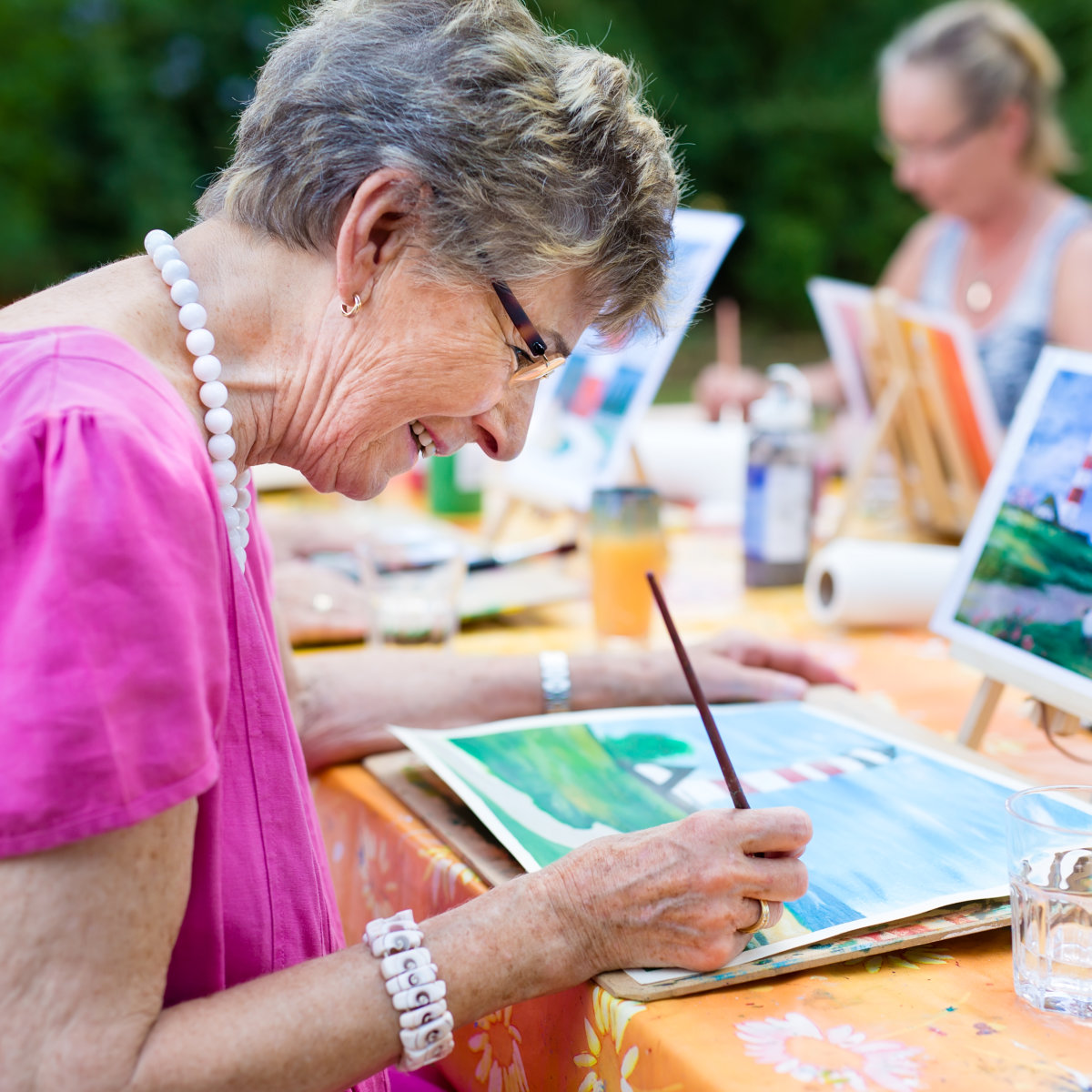 Side view of a happy senior woman smiling while drawing as a recreational activity