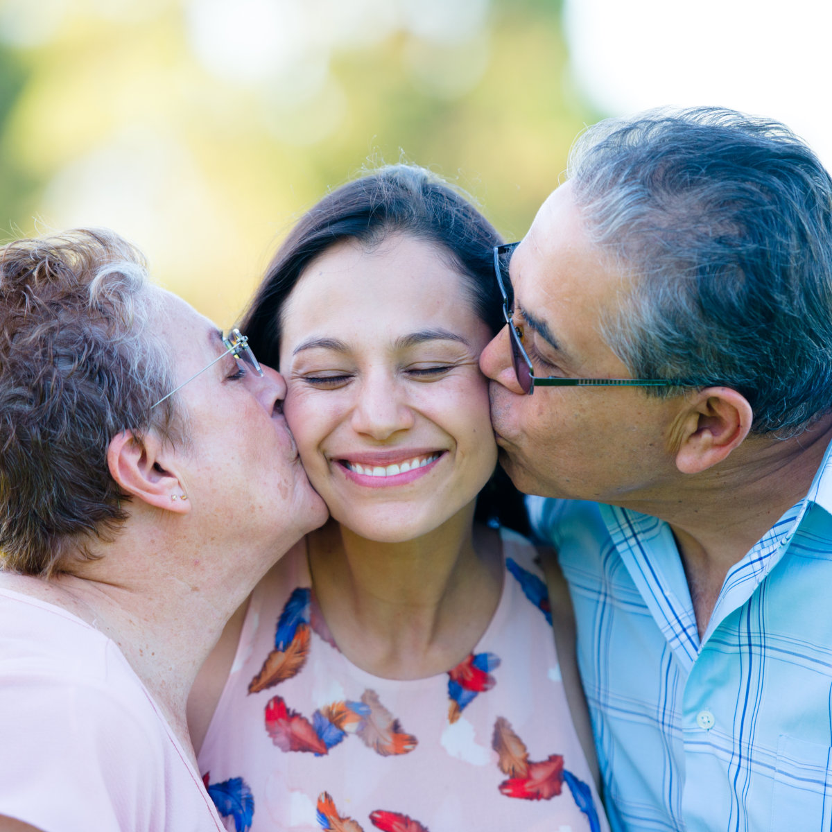 Close up portrait happy parents kissing attractive adult daughter with closed eyes