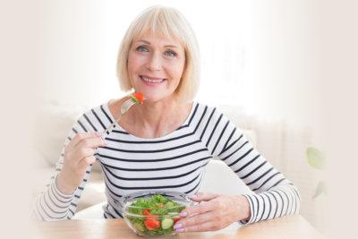 elder woman eating green leafy food
